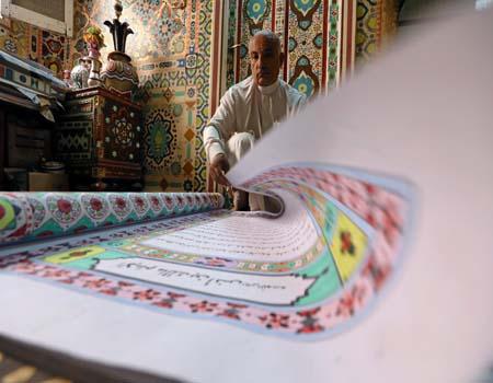 بالصور.. خطاط يرسم مصحفا بخط يده طوله 700 متر لدخول موسوعة جينيس