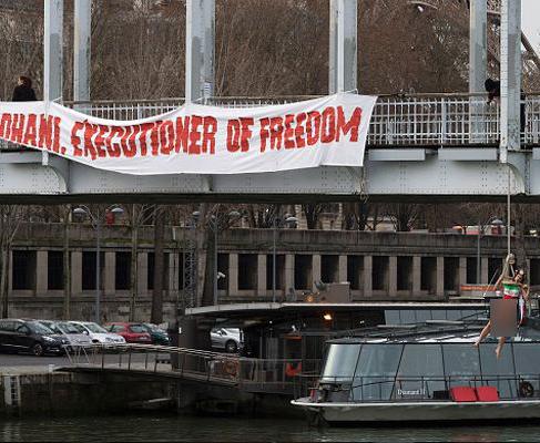 راشا تودی: آویزان شدن یک فمنیست نیمهبرهنه از پلی در پاریس در اعتراض به سفر رئیسجمهور ایران+ تصاویر