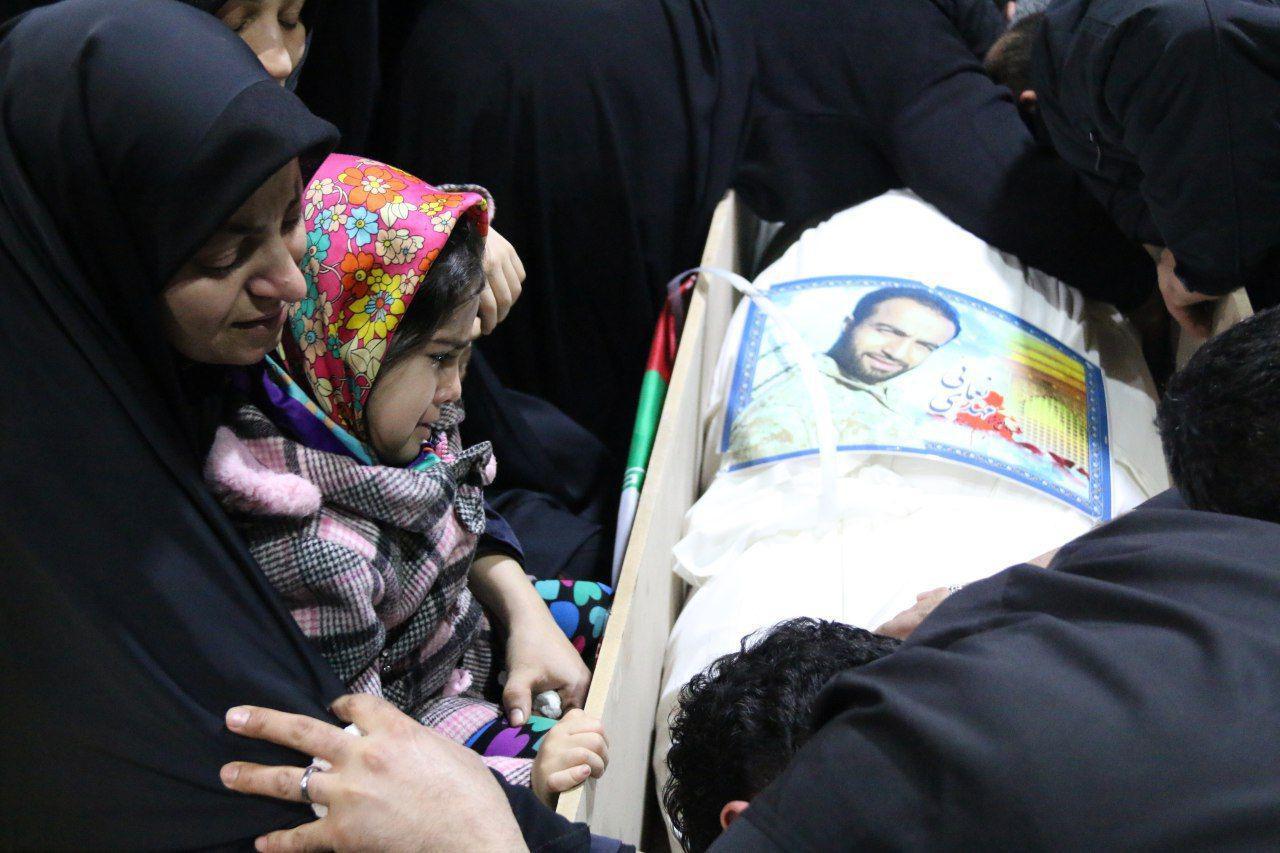 آخرین نگاه فرزند شهید مدافع حرم بر پیکر پدرش +تصویر
