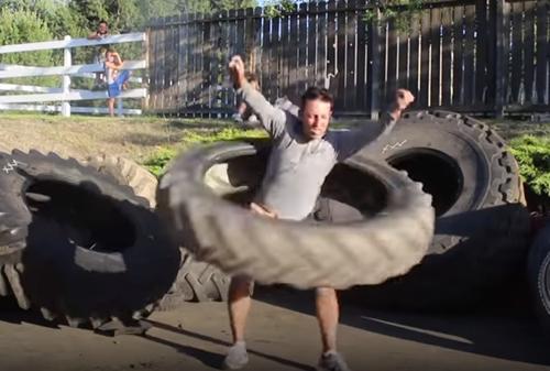 مردی که با لاستیک تراکتور ورزش می کند
