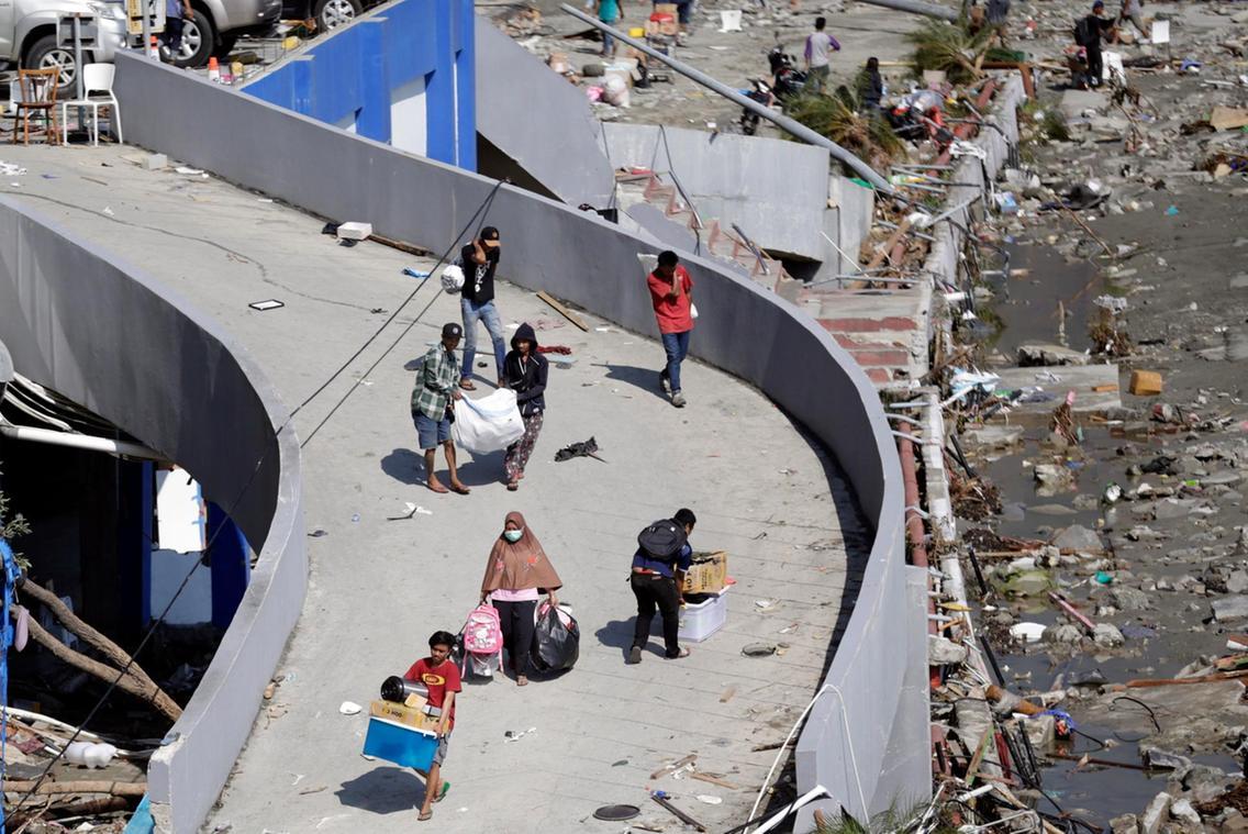 هجوم مردم اندونزی به فروشگاهها به دلیل کمبود غذا/ دفن گروهی قربانیان+ تصاویر