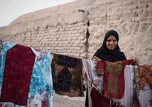 زنی در حال پهن کردن لباس ها در یکی از روستاهای ماهشهر