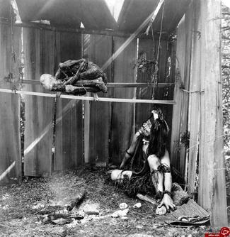 یک سرخپوست بومی آمریکا در حال مومیایی کردن یک جسد با استفاده از دود و ذغال افروخته که در گذشته یکی از روشهای مومیایی به شمار می رفت! ۱۹۱۰ میلادی
