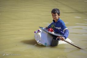 میثم زحمتکش، ۱۱ساله، دانش آموز. حیاط و خانه آنها را آب گرفته است و  او با کیسه و بطری خالی آب برای خودش قایق درست کرده  تا بتواند از خانه بیرون بیاد.