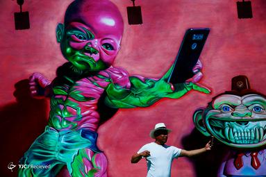 عکس سلفی یک گردشگر با نقاشی دیواری در نمایشگاه میامی