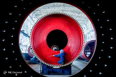 یک کارگر در حال کار کردن بروی دستگاه آسیاب در یک کارخانه در استان جیانگ سو، چین