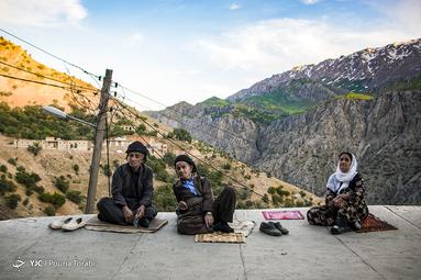 مردم روستای هورامان تخت با لباس محلی بر تن جلو خانه هاش خود نشستهاند