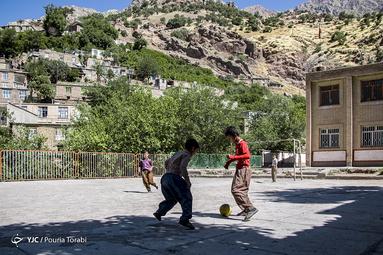 دانش آموزان مدرسه ی روستای ژیوار در حال بازی فوتبال در حیاط مدرسه میباشند