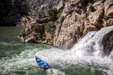 گردشگران در حال قایق سواری در نزدیکی آبشار چشمه بِل در مرز کردستان و کرمانشاه در نزدیکی روستای ناو هستند. مرز کردستان و کرمانشاه در نزدیکی روستای ناو قرار دارد