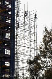کارگران در حال بستن داربست بروی یک ساختمان