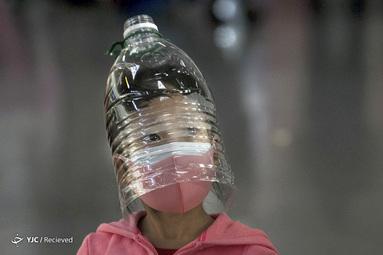 یک دختر چینی ماسک و یک بطری پلاستیکی را برای محافظت از ویروس کرونا به صورت دارد