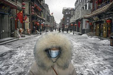 یک زن چینی در خیابان تجاری خالی در پکن چین