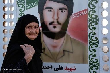 منیژه صحراگرد، مادر شهید علی احمدی هر روز اقدام به تمیز کردن تصویر پسر شهیداش که در خیابان نصب شده میکند - بوشهر